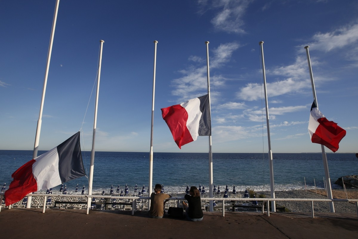 Flags fly at half-mast in memory of victims the day after a truck ran into a crowd at high speed killing scores and injuring more who were celebrating the Bastille Day national holiday, in Nice.