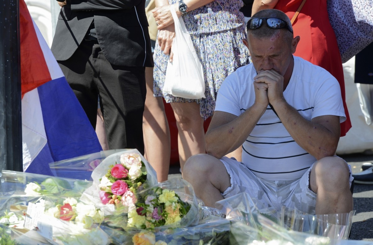 A man reacts by flowers left in tribute to the victims near the scene where a truck ran into a crowd at high speed killing scores and injuring more who were celebrating the Bastille Day national holiday, in Nice.