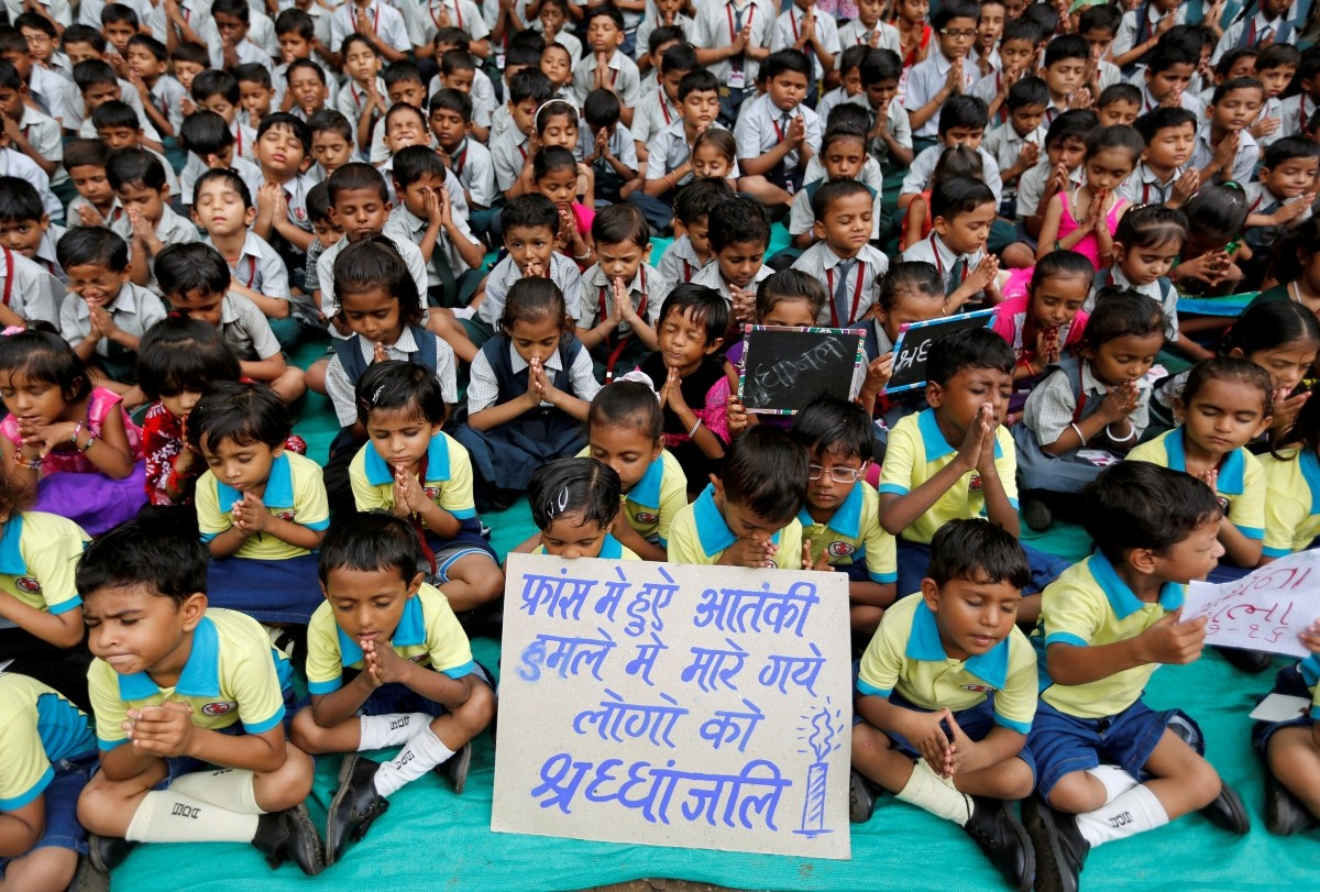 School children offer prayers at a school in Ahmedabad, India, July 15, 2016. The placard reads,