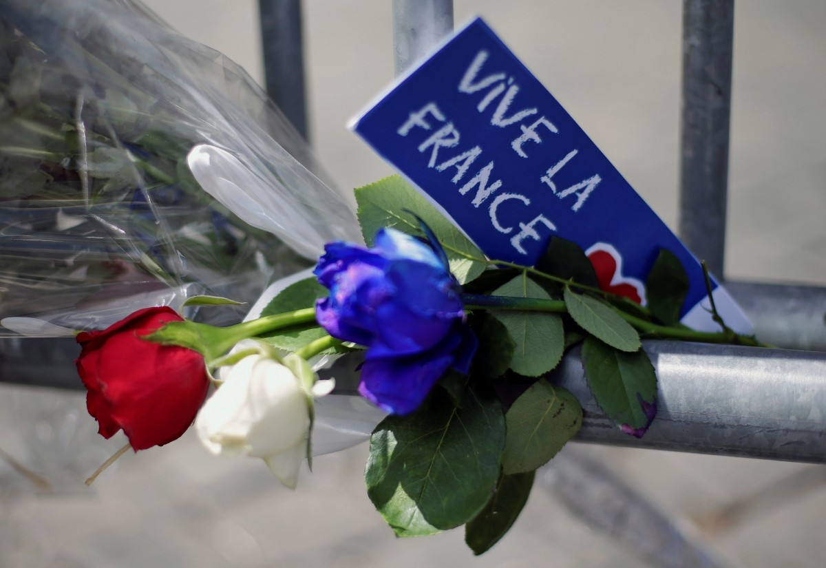 Flowers are seen attached to a fence to remember the victims in front of the French embassy in Rome, Italy, July 15, 2016.