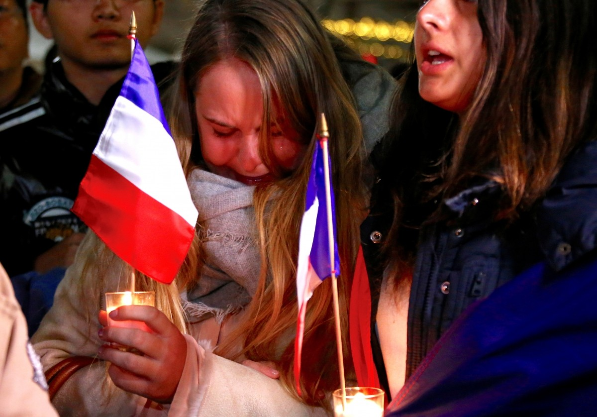 Members of the Australian French community cry as they sing the French national anthem during a vigil in central Sydney, Australia, July 15, 2016.