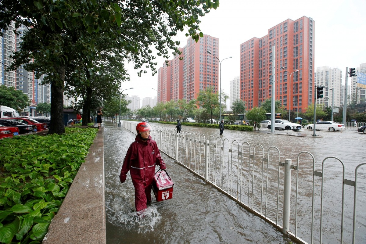 A food deliveryman wades through a flooded street during a heavy rainfall in Shilipu, Chaoyang Road, Beijing, China, July 20, 2016.