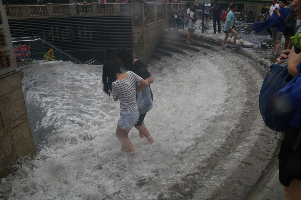 People walk into a flooded subway station in Tianjin, China, July 20, 2016.