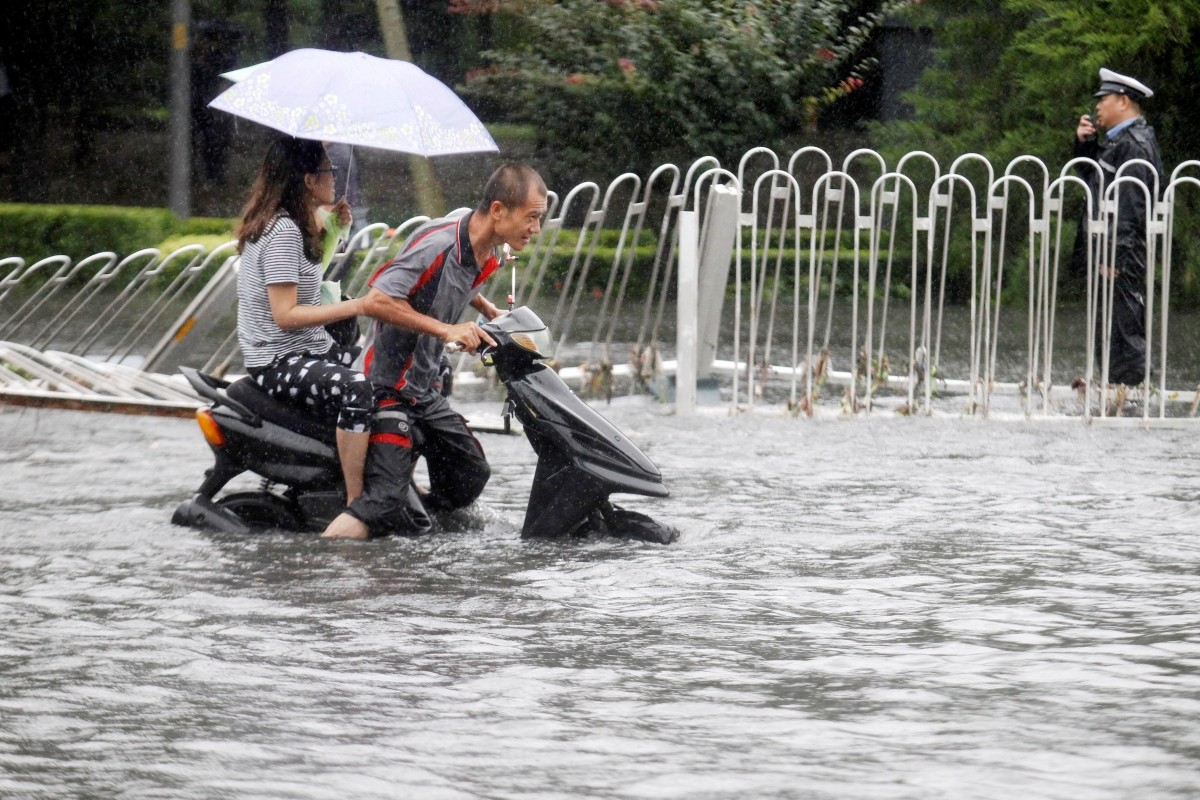People ride along a flooded street during a heavy rainfall in Beijing, China, July 20, 2016