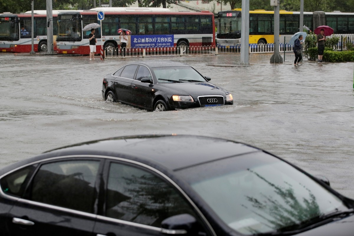 Cars go through a flooded street during a heavy rainfall in Shilipu, Chaoyang Road, Beijing, China, July 20, 2016.