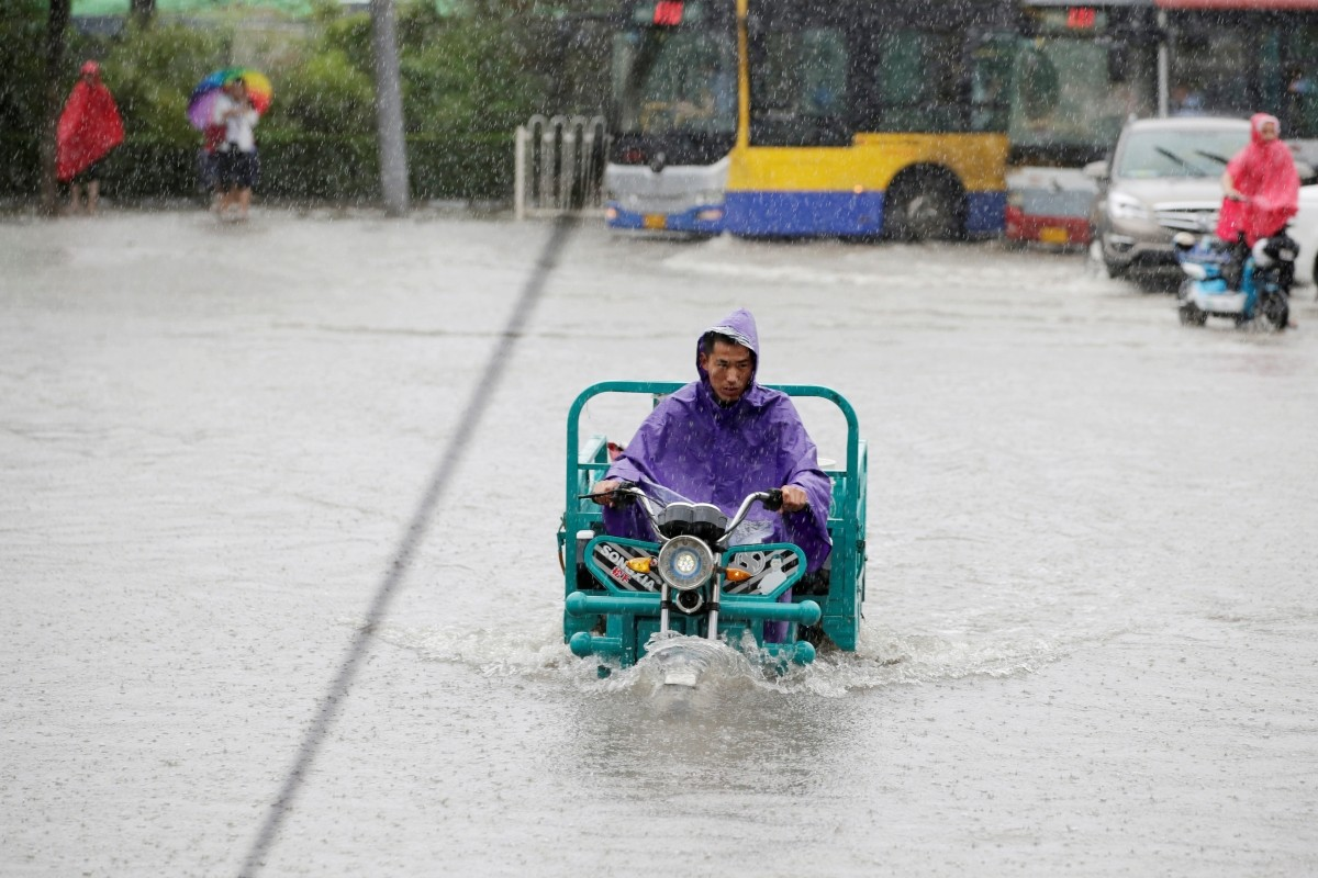 A man rides through a flooded street during a heavy rainfall in Shilipu, Chaoyang Road, Beijing, China, July 20, 2016.