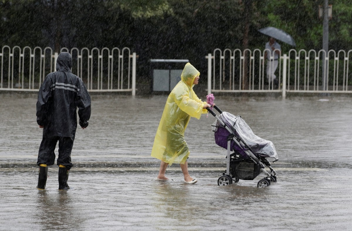 A woman pushes a baby stroller along a flooded street during a heavy rainfall in Shilipu, Chaoyang Road, Beijing, China July 20, 2016.