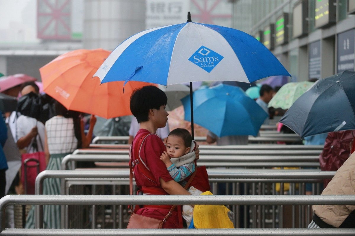 A woman carries a baby as she enters Beijing West Railway Station during a heavy rainfall in Beijing, China, July 20, 2016.