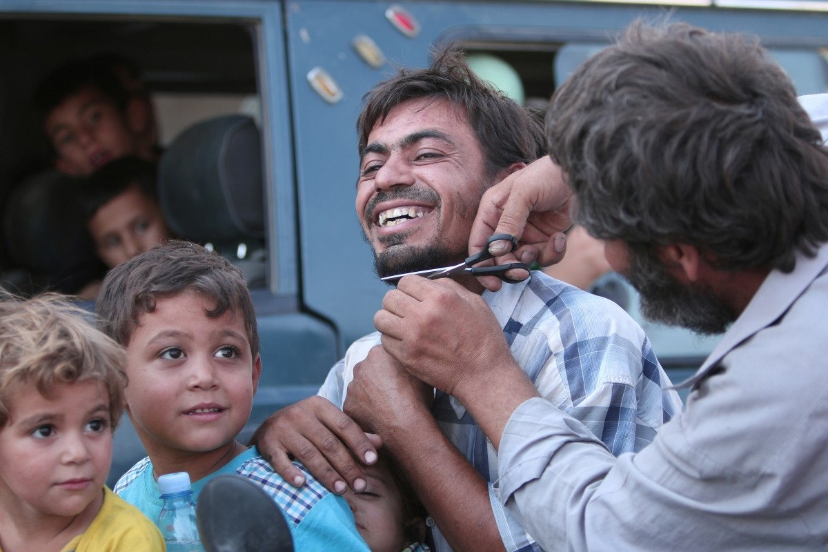 A man cuts the beard of a civilian who was evacuated with others by the Syria Democratic Forces (SDF) fighters from an Islamic State-controlled neighbourhood of Manbij, in Aleppo Governorate, Syria, August 12, 2016. The SDF has said Islamic State was using civilians as human shields.