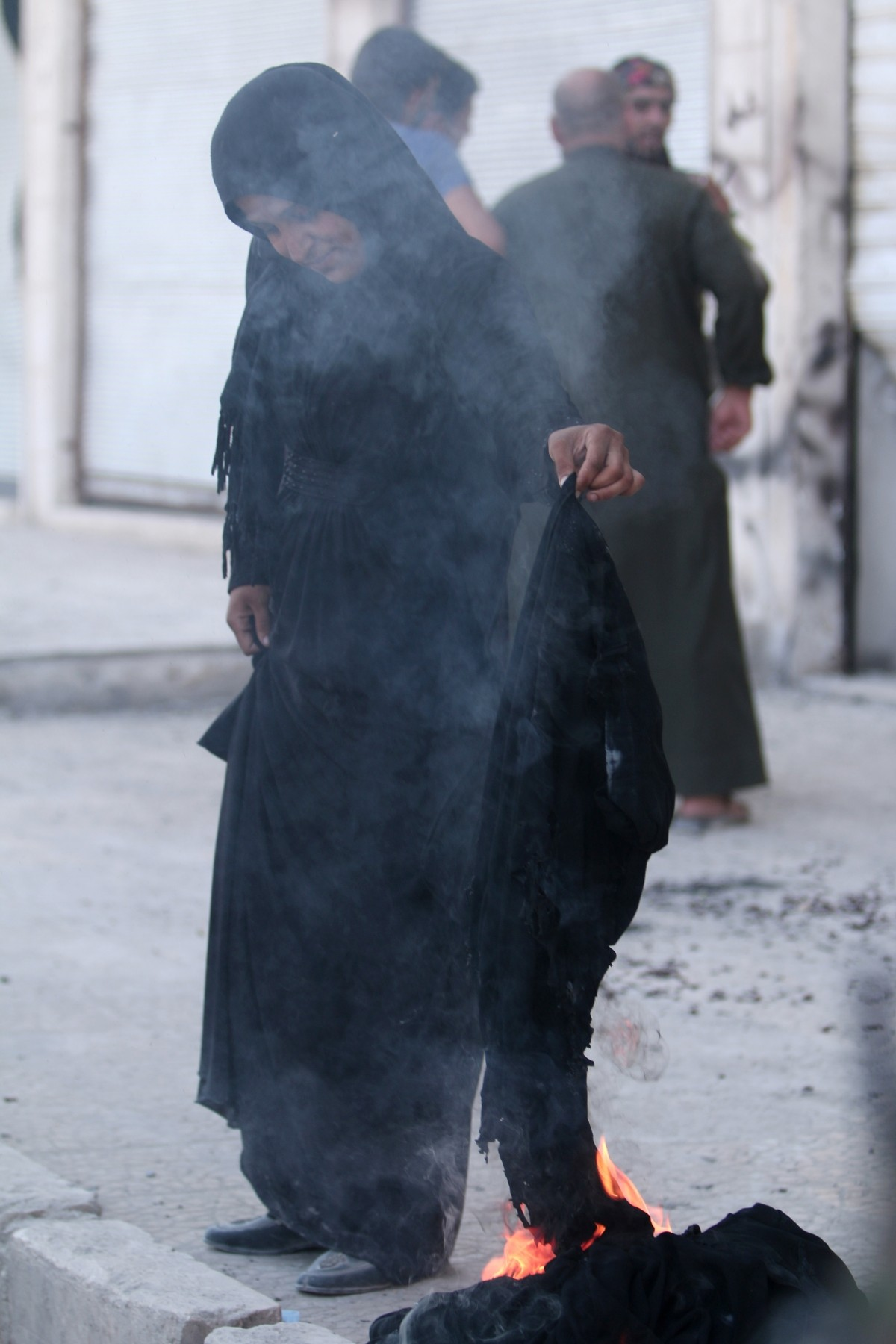 A woman sets fire to a niqab after she was evacuated with others by the Syria Democratic Forces (SDF) fighters from an Islamic State-controlled neighbourhood of Manbij, in Aleppo Governorate, Syria, August 12, 2016. The SDF has said Islamic State was using civilians as human shields.