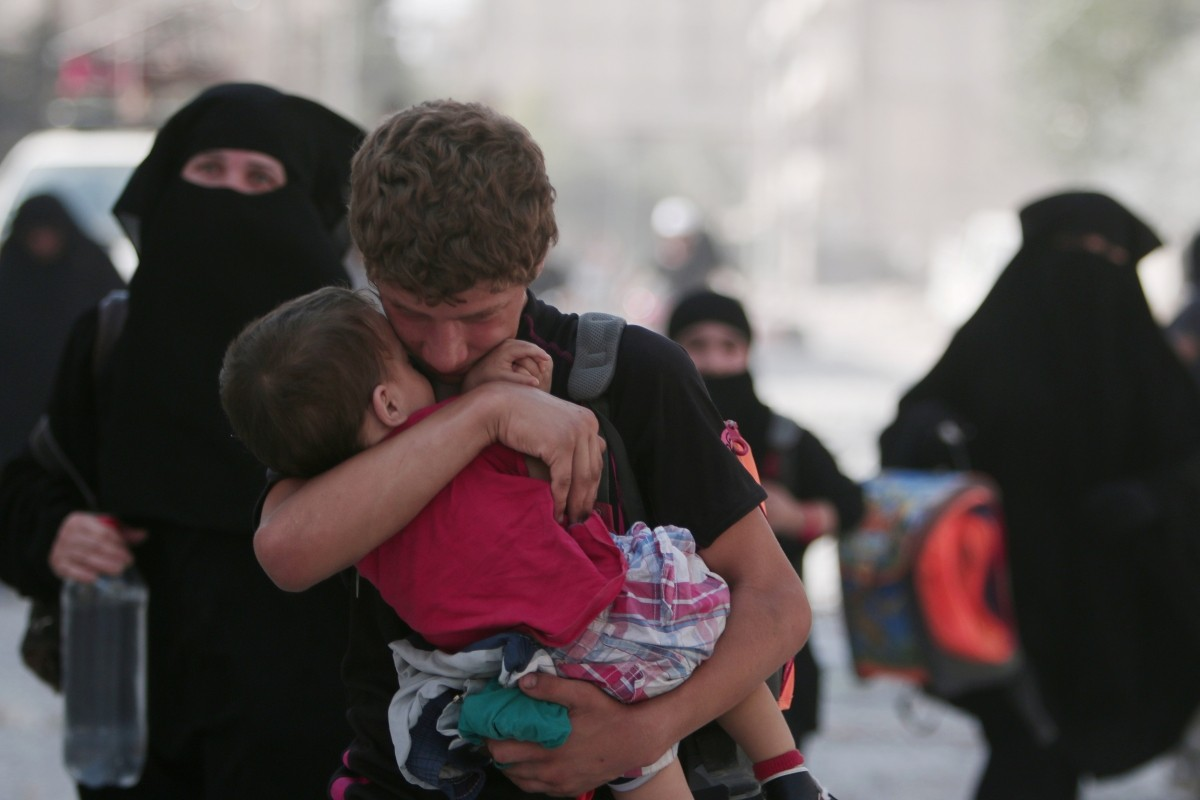 A civilian carries a child as he walks with others after they were evacuated by the Syria Democratic Forces (SDF) fighters from an Islamic State-controlled neighbourhood of Manbij, in Aleppo Governorate, Syria, August 12, 2016. The SDF has said Islamic State was using civilians as human shields.
