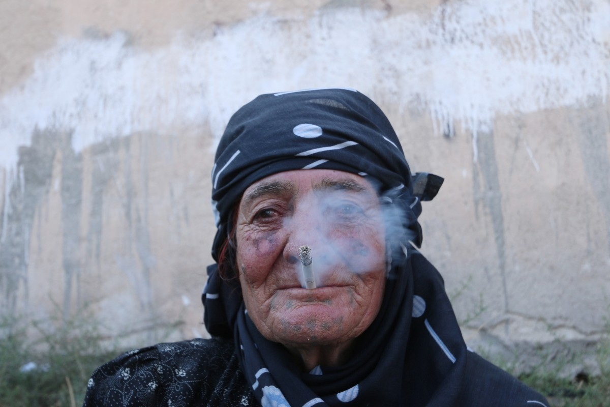 A woman smokes as she rests after she was evacuated with others by the Syria Democratic Forces (SDF) fighters from an Islamic State-controlled neighbourhood of Manbij, in Aleppo Governorate, Syria, August 12, 2016. The SDF has said Islamic State was using civilians as human shields.