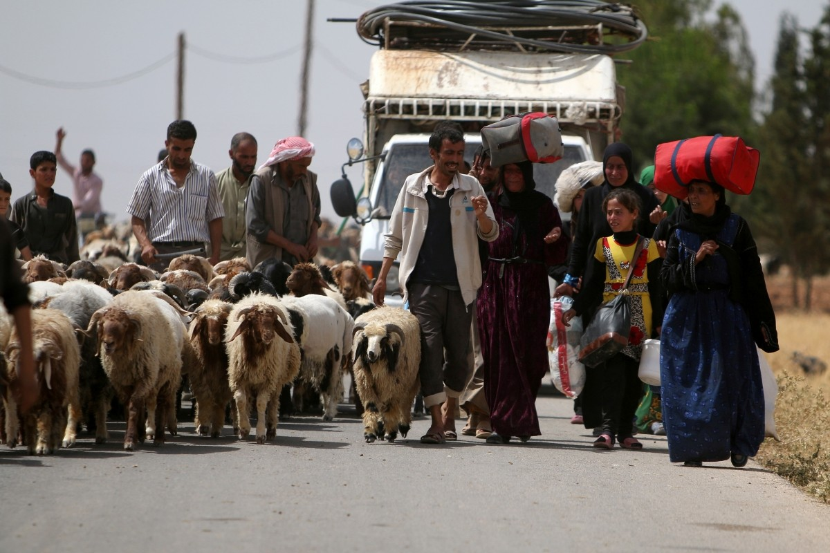 Civilians, who fled the violence in Manbij city, carry their belongings as they walk with their herd of sheep upon their arrival to the southeastern rural area of Manbij, in Aleppo Governorate, Syria June 19, 2016.