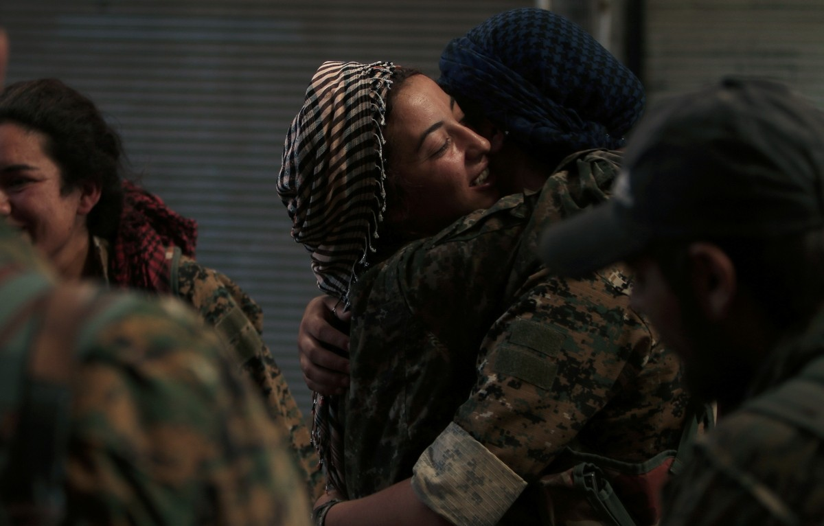 Syria Democratic Forces (SDF) female fighters embrace each other in the city of Manbij, in Aleppo Governorate, Syria, August 10, 2016.