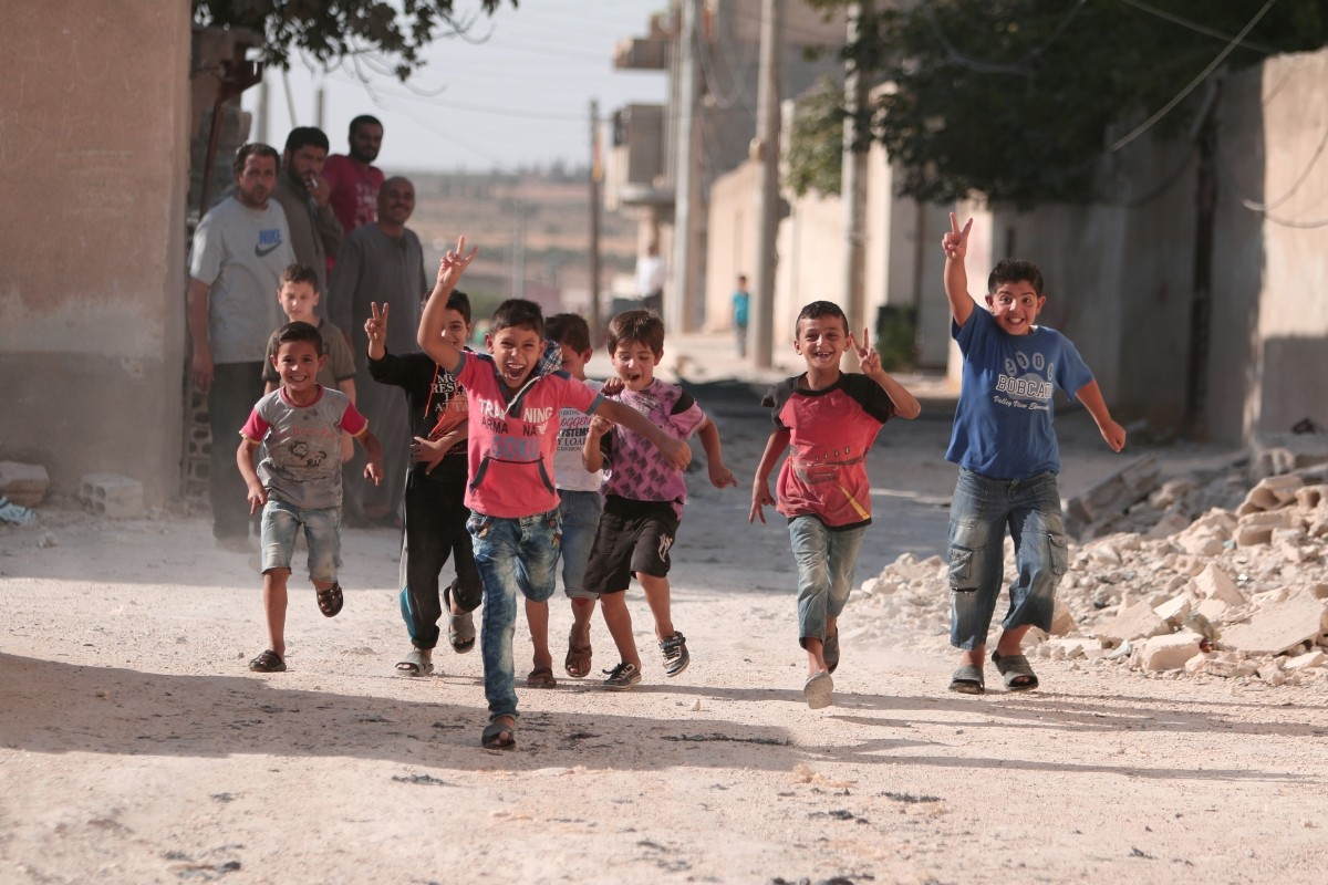 Children flash victory signs as they play in Manbij, in Aleppo Governorate, Syria, August 9, 2016.