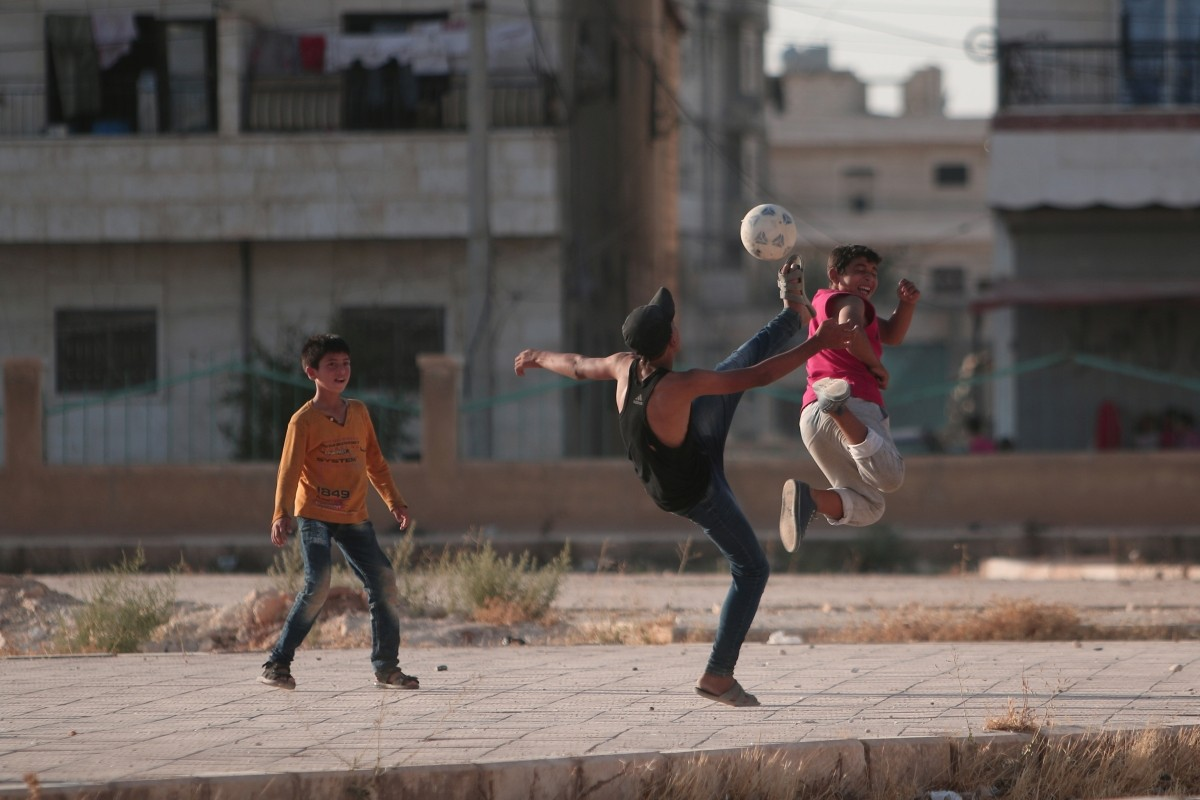 Youths play soccer on a street in Manbij, in Aleppo Governorate, Syria, August 9, 2016.