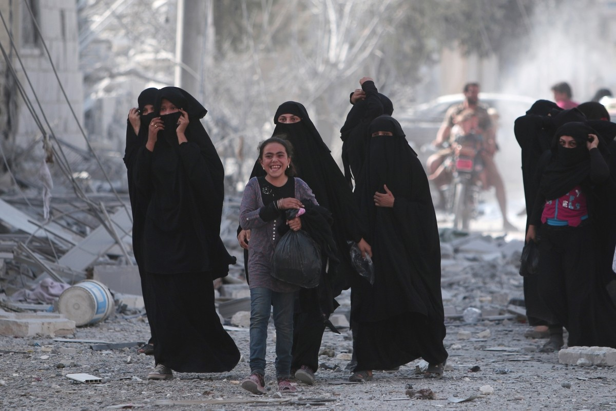 A girl reacts while walking with women after they were evacuated with others by the Syria Democratic Forces (SDF) fighters from an Islamic State-controlled neighbourhood of Manbij, in Aleppo Governorate, Syria, August 12, 2016. The SDF has said Islamic State was using civilians as human shields.