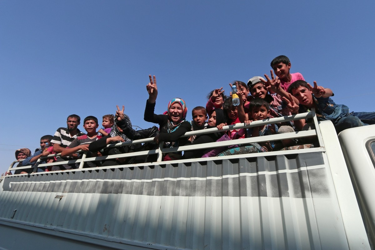 Civilians react atop of a pick-up truck after they were evacuated by the Syria Democratic Forces (SDF) fighters from an Islamic State-controlled neighbourhood of Manbij, in Aleppo Governorate, Syria, August 12, 2016. The SDF has said Islamic State was using civilians as human shields.