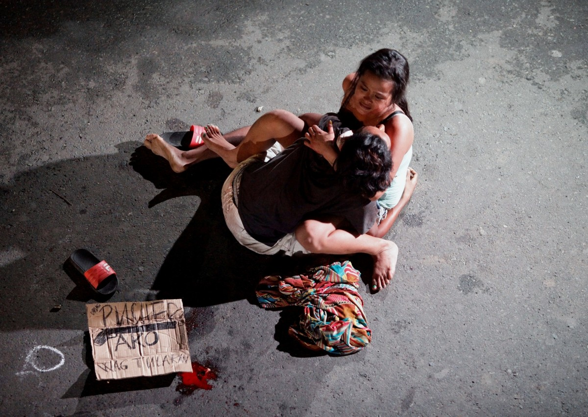 Jennelyn Olaires, 26, weeps over the body of her partner, who was killed on a street by a vigilante group, according to police, in a spate of drug related killings in Pasay city, Metro Manila, Philippines July 23, 2016. A sign on a cardboard found near the body reads: