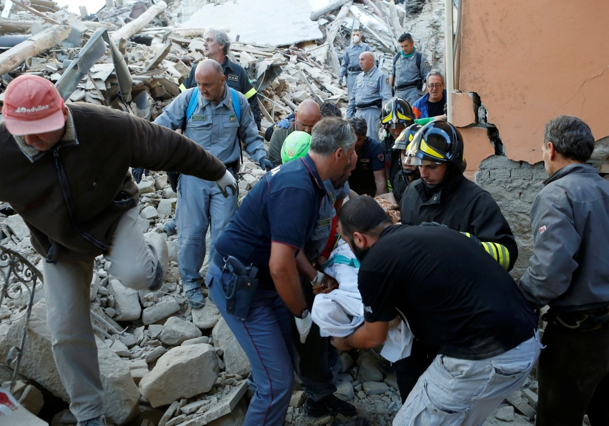 Rescuers carry a person on a stretcher following a quake in Amatrice, central Italy, August 24, 2016.