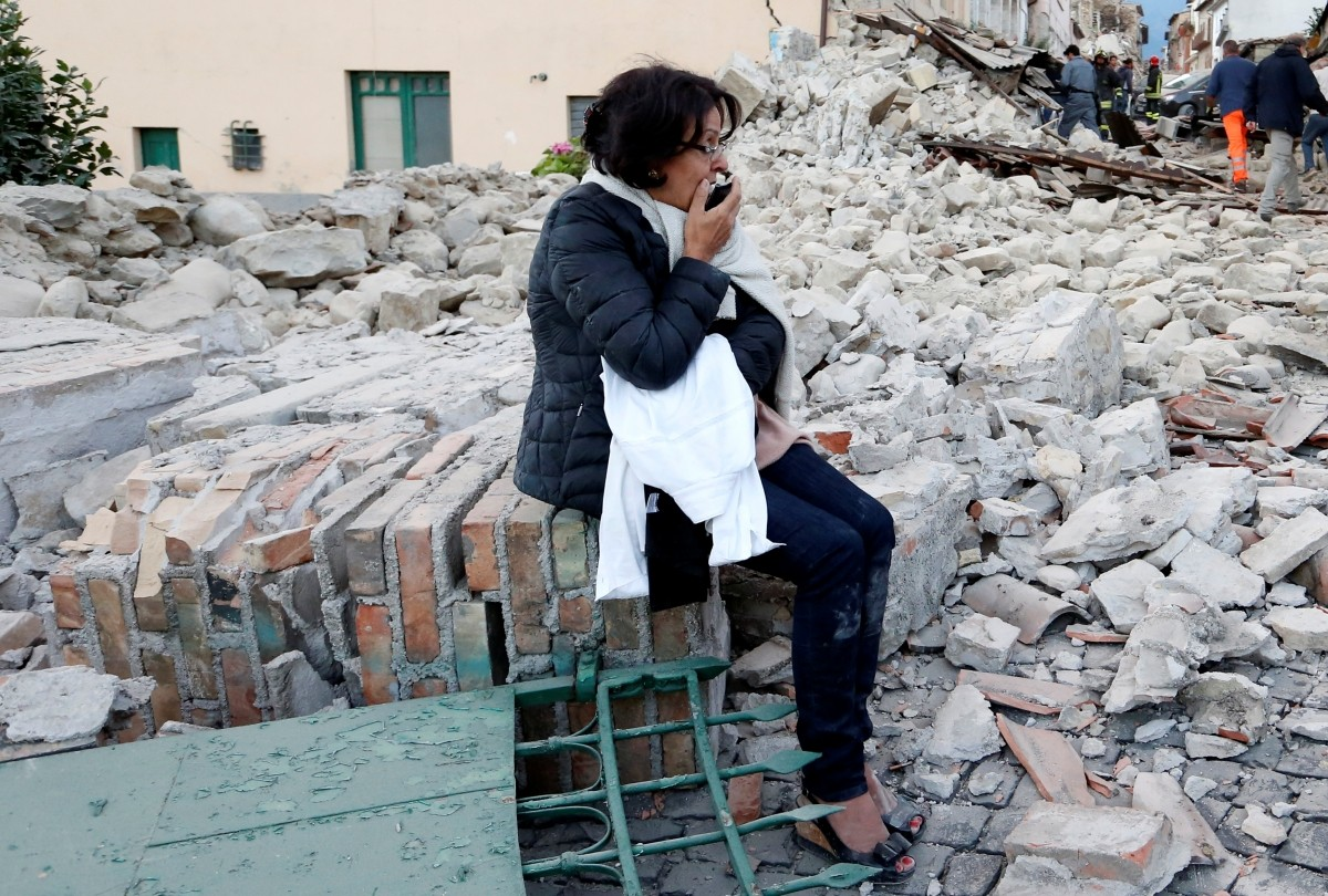 A woman sits amongst rubble following a quake in Amatrice, central Italy, August 24, 2016.