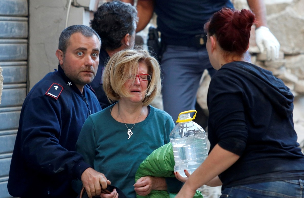 A woman (2nd L) cries after been rescued from her home following a quake in Amatrice, central Italy, August 24, 2016.
