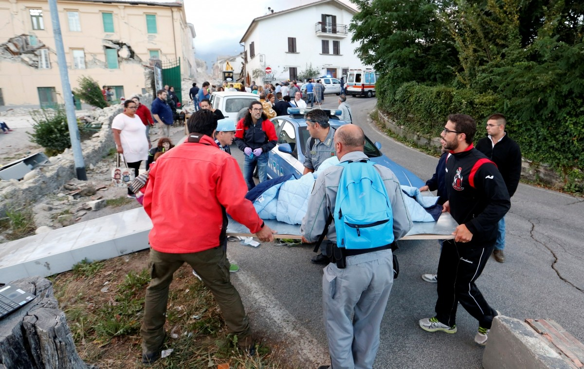 People stand along the road following a quake in Amatrice, central Italy, August 24, 2016.