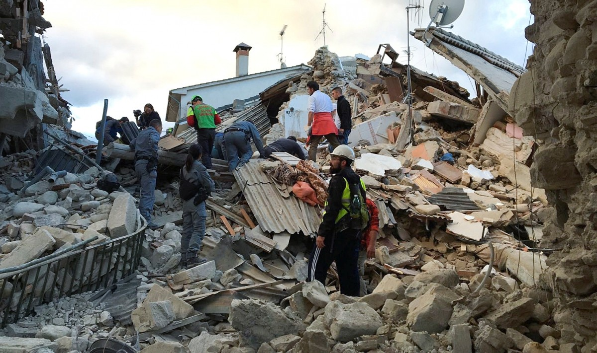 Rescuers work at a collapsed house following a quake in Amatrice, central Italy, August 24, 2016.