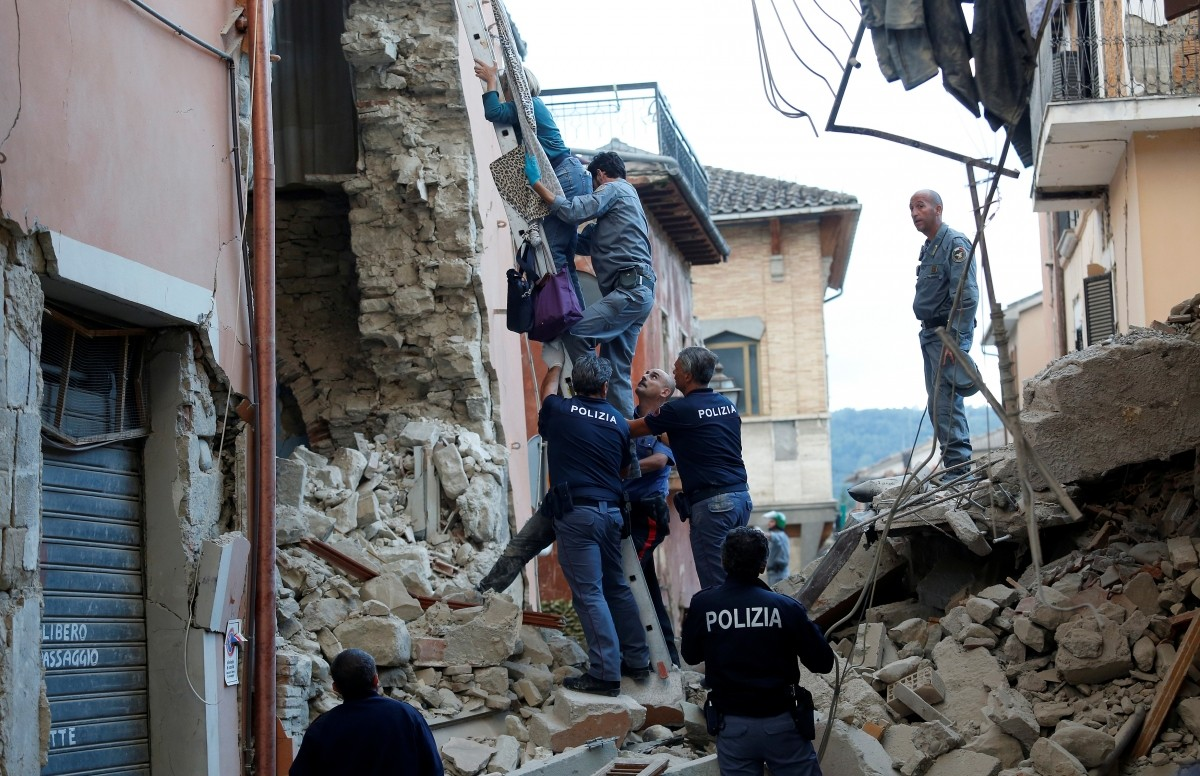 A woman is helped to leave her home by rescuers following a quake in Amatrice, central Italy, August 24, 2016.