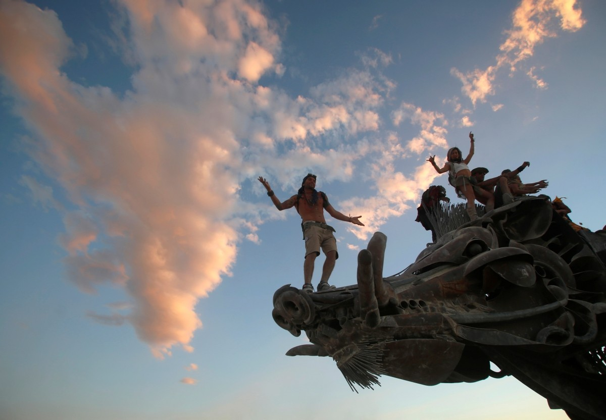 Participants dance and climb on an art installation as approximately 70,000 people from all over the world gather for the 30th annual Burning Man arts and music festival in the Black Rock Desert of Nevada, U.S. August 31, 2016.
