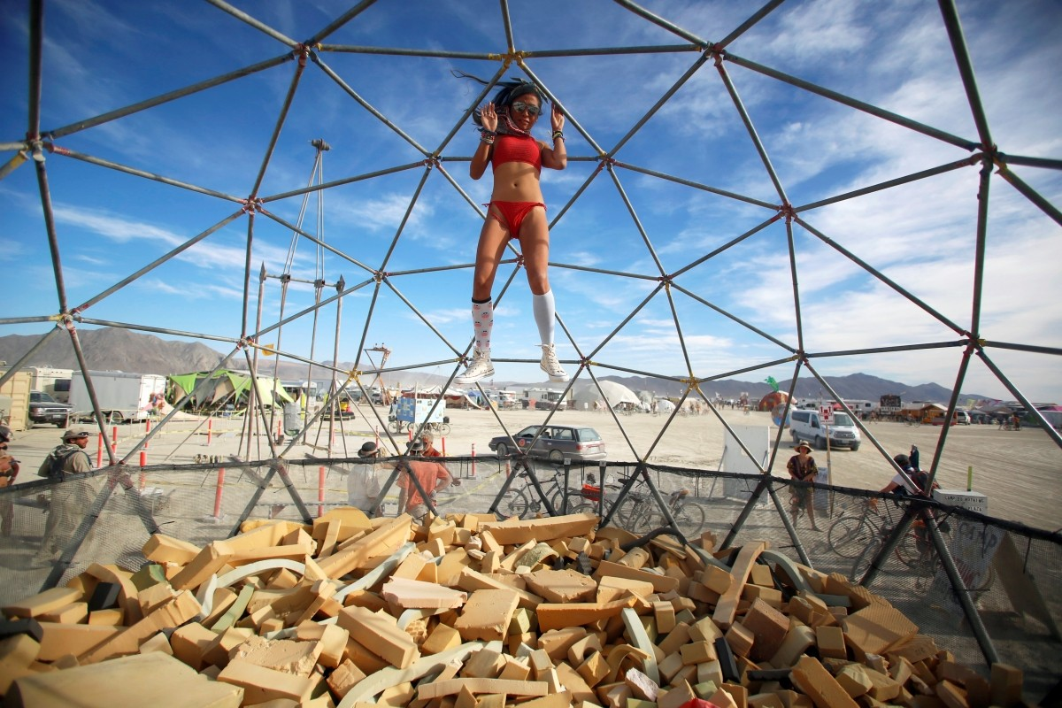 Lulu, her Playa name, falls into a foam pit as approximately 70,000 people from all over the world gather for the 30th annual Burning Man arts and music festival in the Black Rock Desert of Nevada, U.S. September 1, 2016.