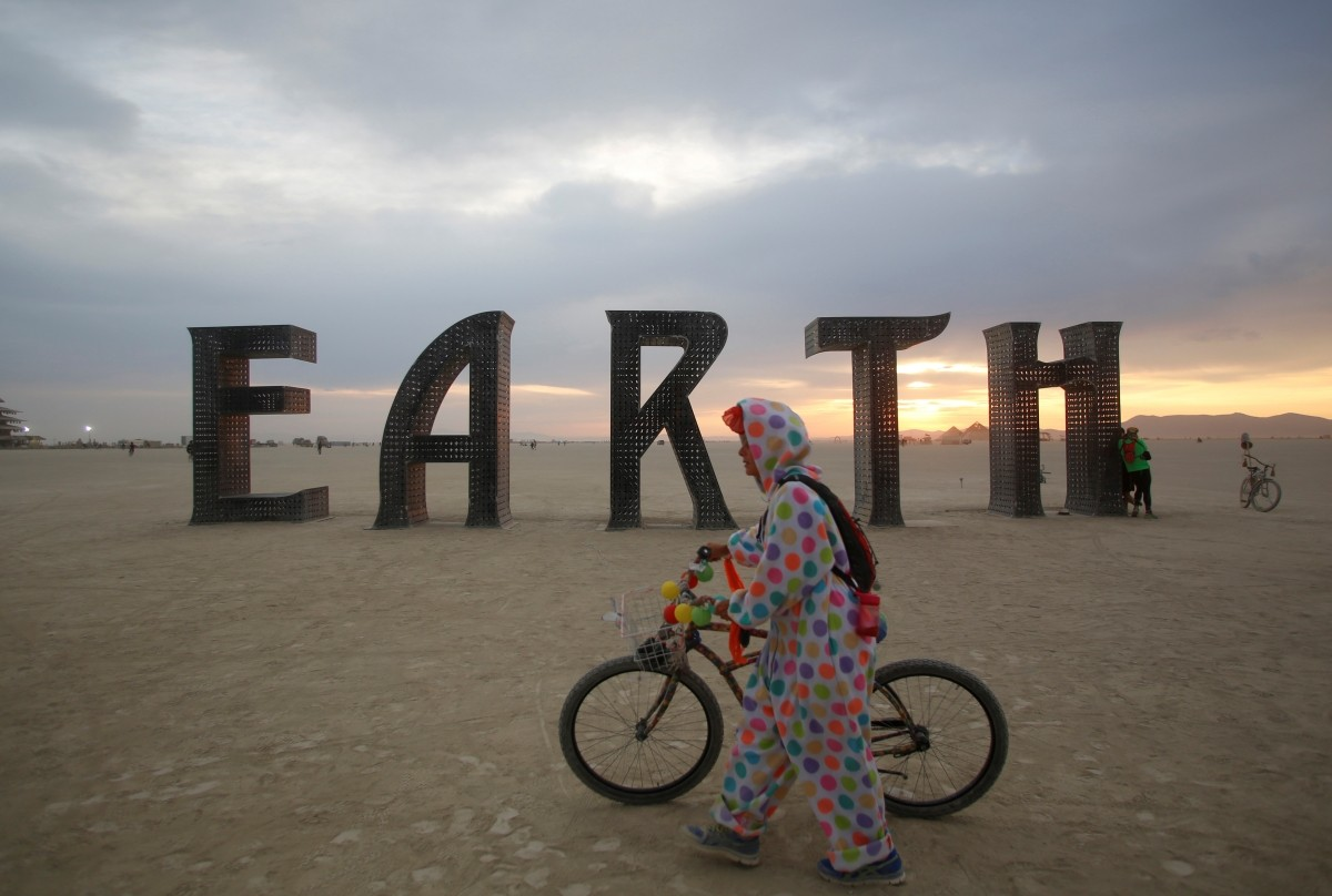 A participant walks past an art installation as approximately 70,000 people from all over the world gather for the 30th annual Burning Man arts and music festival in the Black Rock Desert of Nevada, U.S. August 30, 2016.