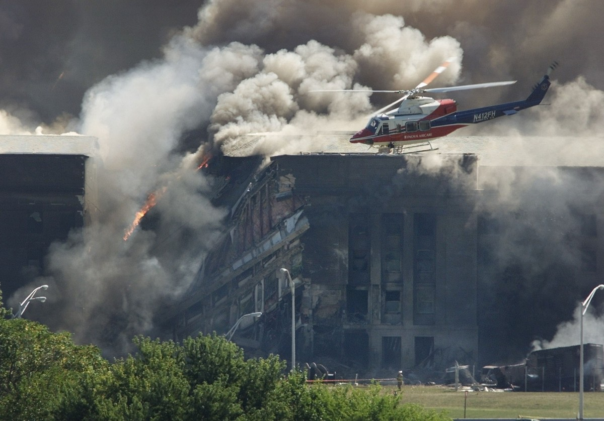 A rescue helicopter surveys damage to the Pentagon as firefighters battle flames after a hijacked airplane crashed into the U.S. military headquarters outside of Washington, September 11, 2001.