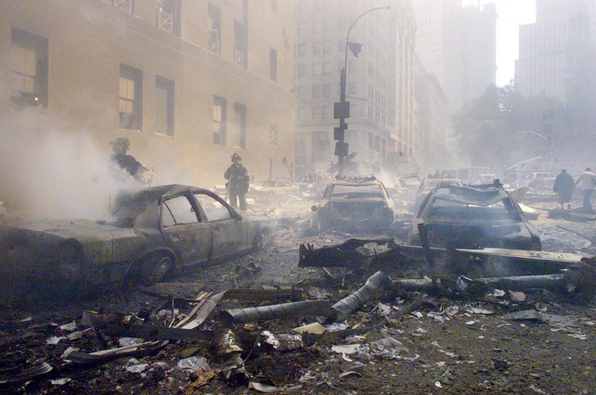 Cars smolder in the street as the destroyed World Trade Center burns in New York on September 11, 2001.