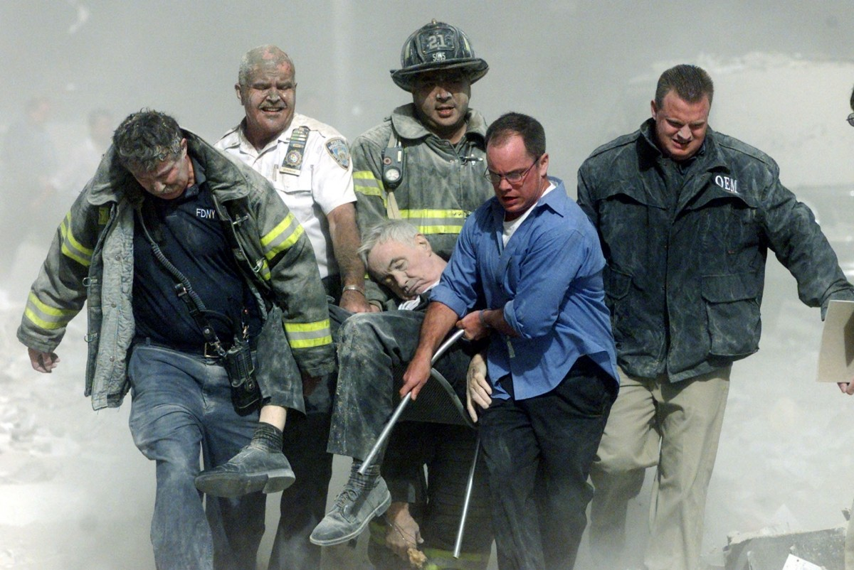 Rescue workers carry mortally injured New York City Fire Department chaplain, the Rev. Mychal Judge, from the wreckage of the World Trade Center in New York City September 11, 2001. The Chaplain was crushed to death by falling debris while giving a man last rites in the trade center.