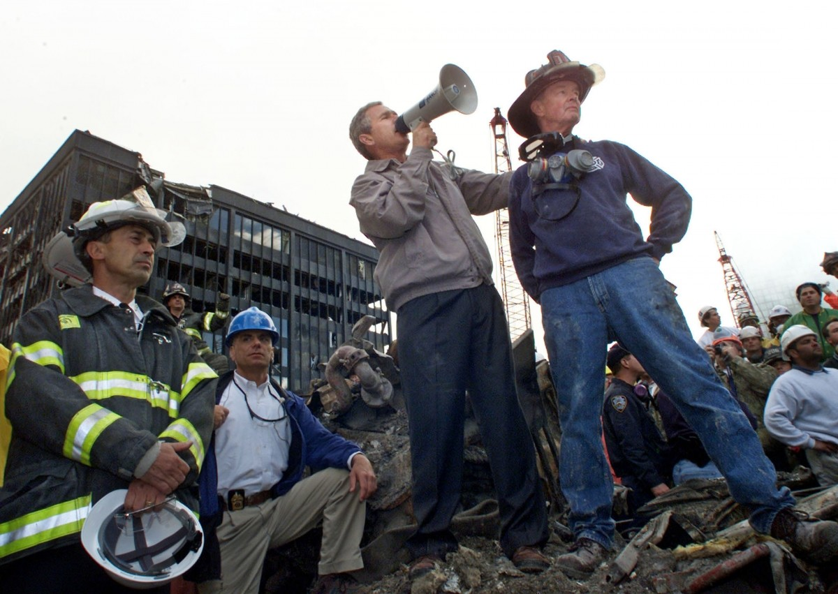 Then President Bush is shown with retired firefighter Bob Beckwith (R) at the scene of the World Trade Center disaster on September 14, 2001.
