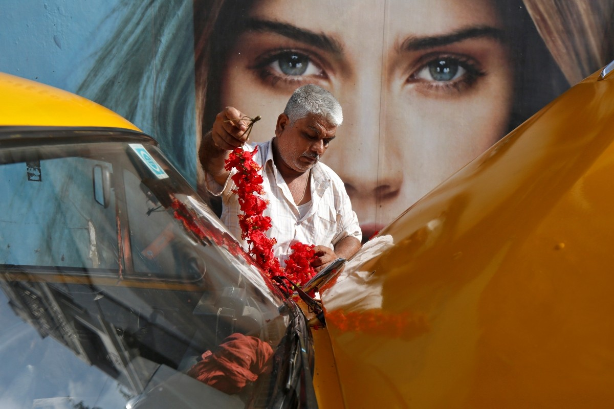 A taxi driver decorates his car before offering prayers during the Vishwakarma Puja festival in Kolkata, India, September 17, 2016