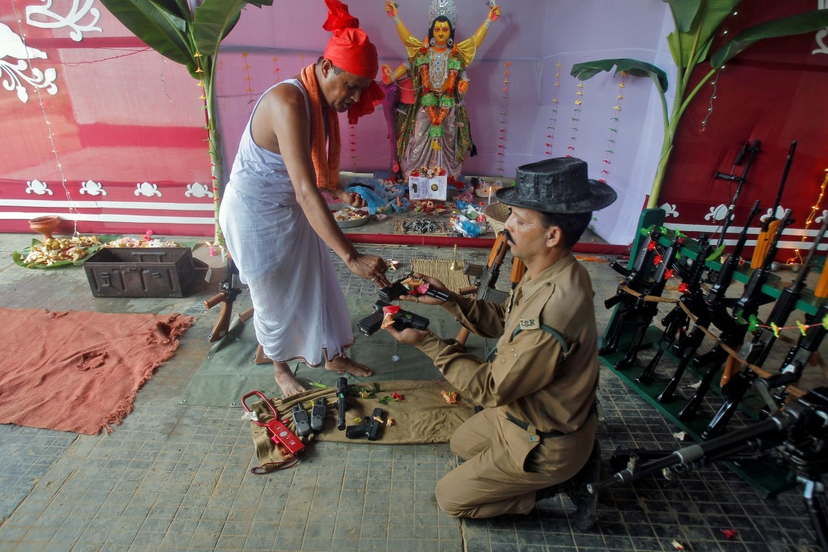 A police officer has weapons blessed by a Hindu priest during the Vishwakarma Puja festival in the outskirts of Agartala, India, September 17, 2016.
