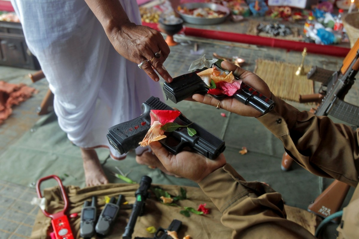 A police officer has weapons blessed by a Hindu priest during the Vishwakarma Puja festival on the outskirts of Agartala, India, September 17, 2016.