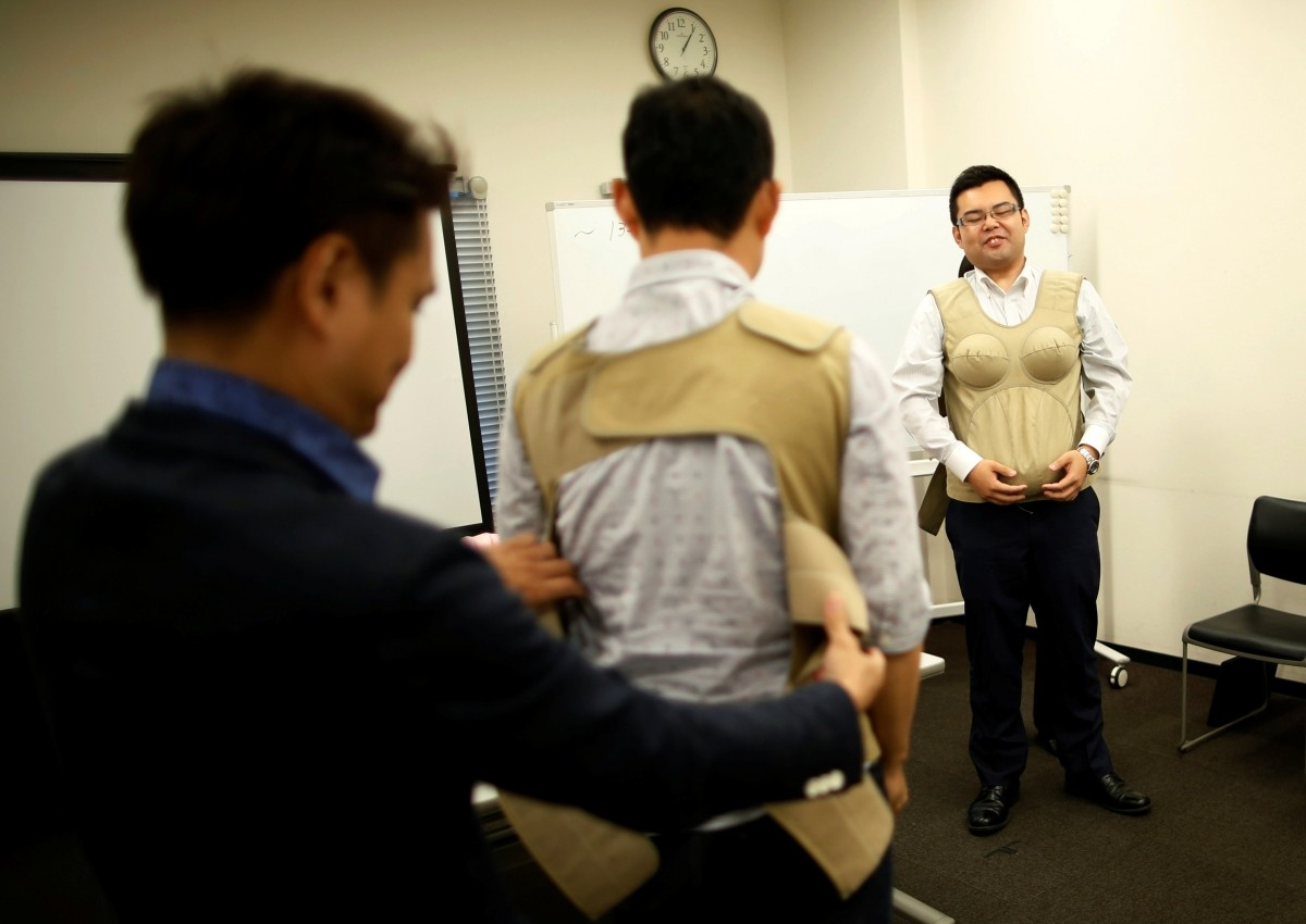 Participants try to wear 7-kilogram pregnancy jackets as they take part in an