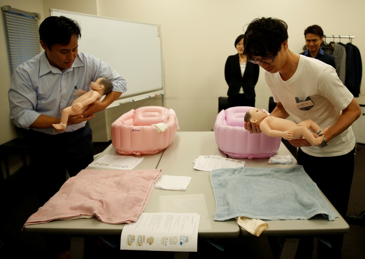 Takashi Tayama (front R), 35, and Yuji Inoue (L), 42, take part in a