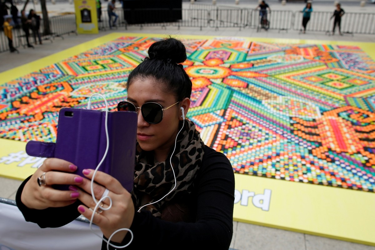 A woman takes a selfie with 26,896 cans of Play-Doh, a Guinness World Records attempt for the biggest mosaic, inspired by indigenous Huichol art, during a promotional event celebrating the product's 60th anniversary, in Mexico City, Mexico September 23, 2016.