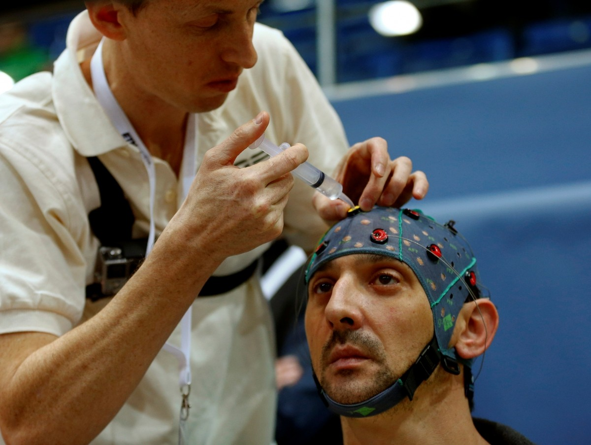 A team member puts contact gel on the cap of Andre Neyron of France before the Brain-Computer Interface Race (BCI) at the Cybathlon Championships in Kloten, Switzerland October 8, 2016.