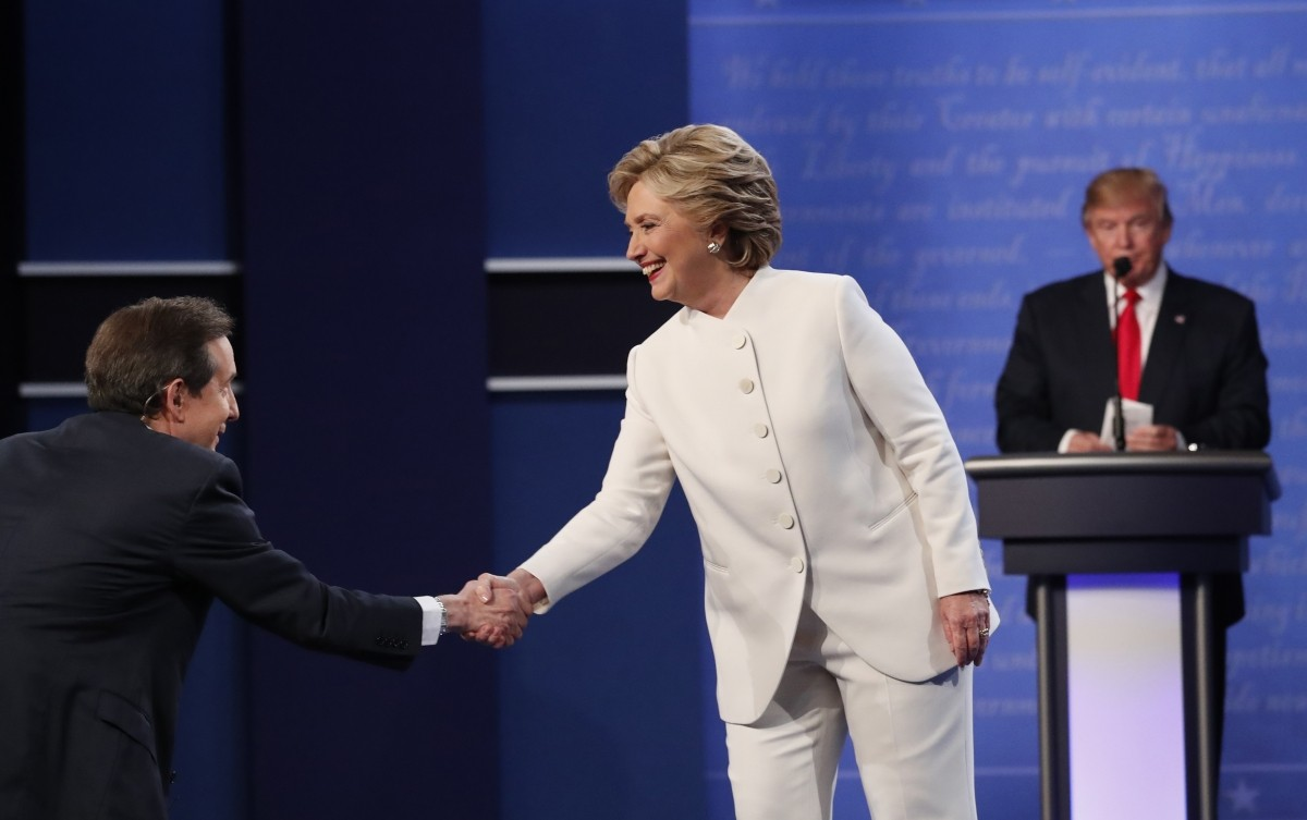 Democratic U.S. presidential nominee Hillary Clinton shakes hands with moderator Chris Wallace (L) as Republican U.S. presidential nominee Donald Trump remains at his podium after the conclusion of their third and final 2016 presidential campaign debate at UNLV in Las Vegas, Nevada, U.S., October 19, 2016.
