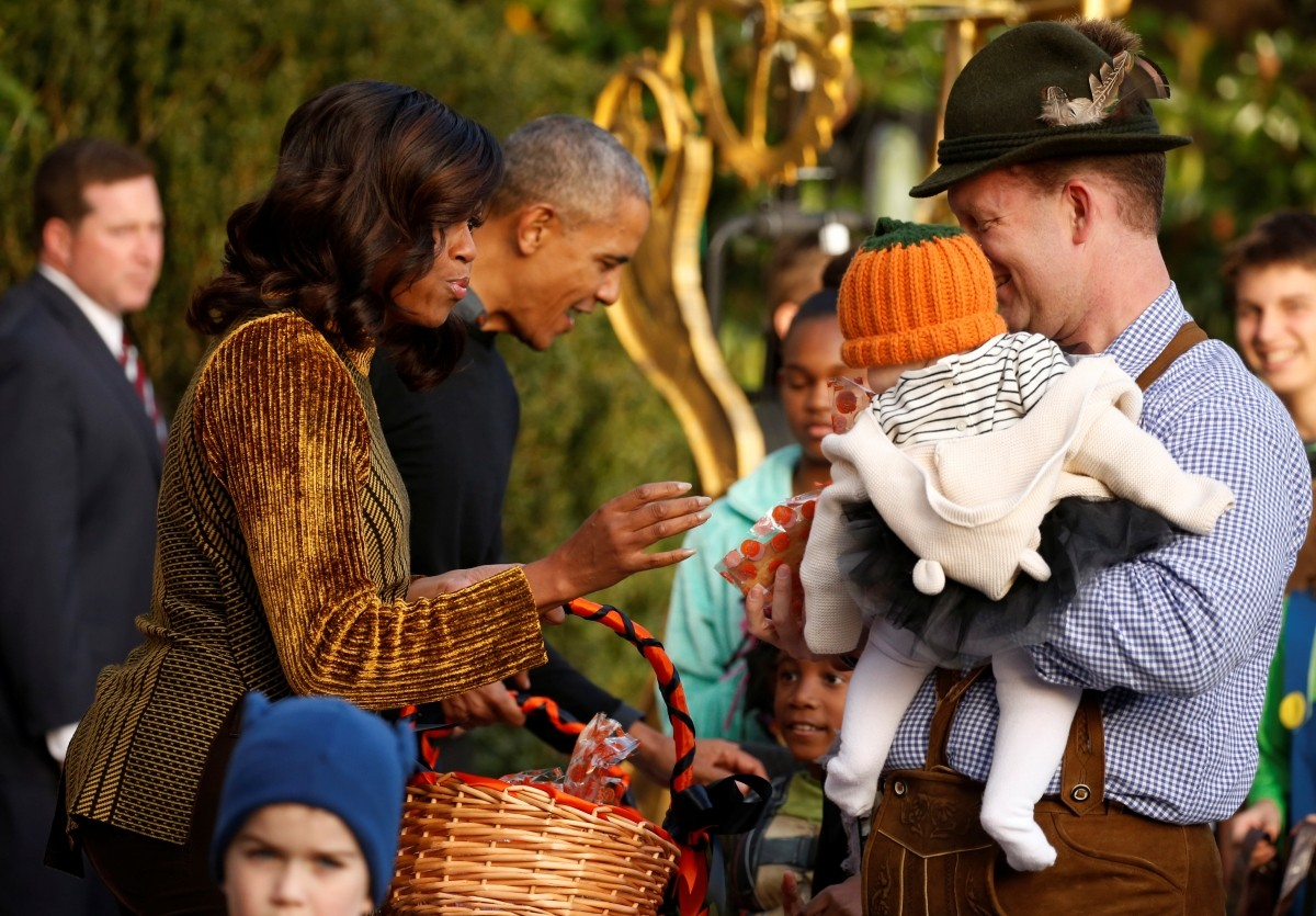 U.S. President Barack Obama and first lady Michelle Obama (L) give out Halloween treats to children from the South Portico of the White House in Washington, U.S. October 31, 2016.