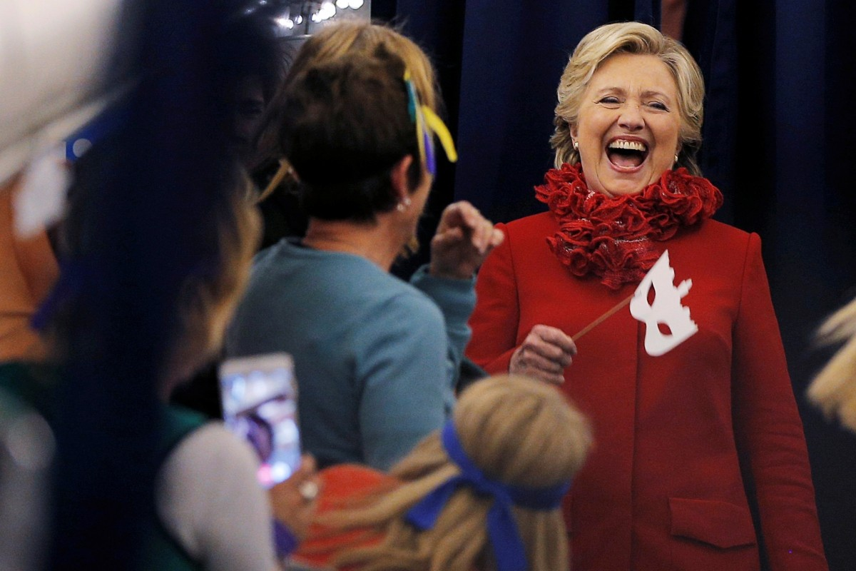 U.S. Democratic presidential nominee Hillary Clinton holds a Halloween mask while joking with her staff on her campaign plane in Erlanger, Kentucky, U.S. October 31, 2016.