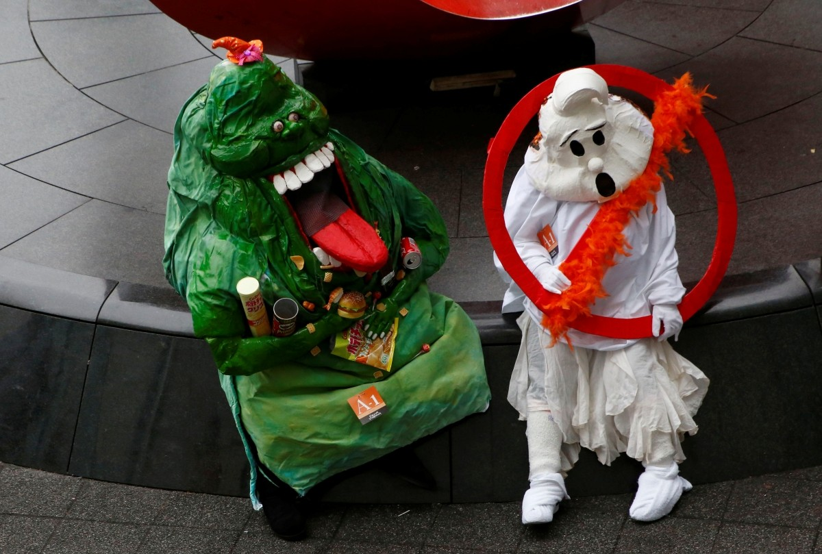 Participants in costumes sit on a bench after a Halloween parade in Kawasaki, south of Tokyo, Japan.