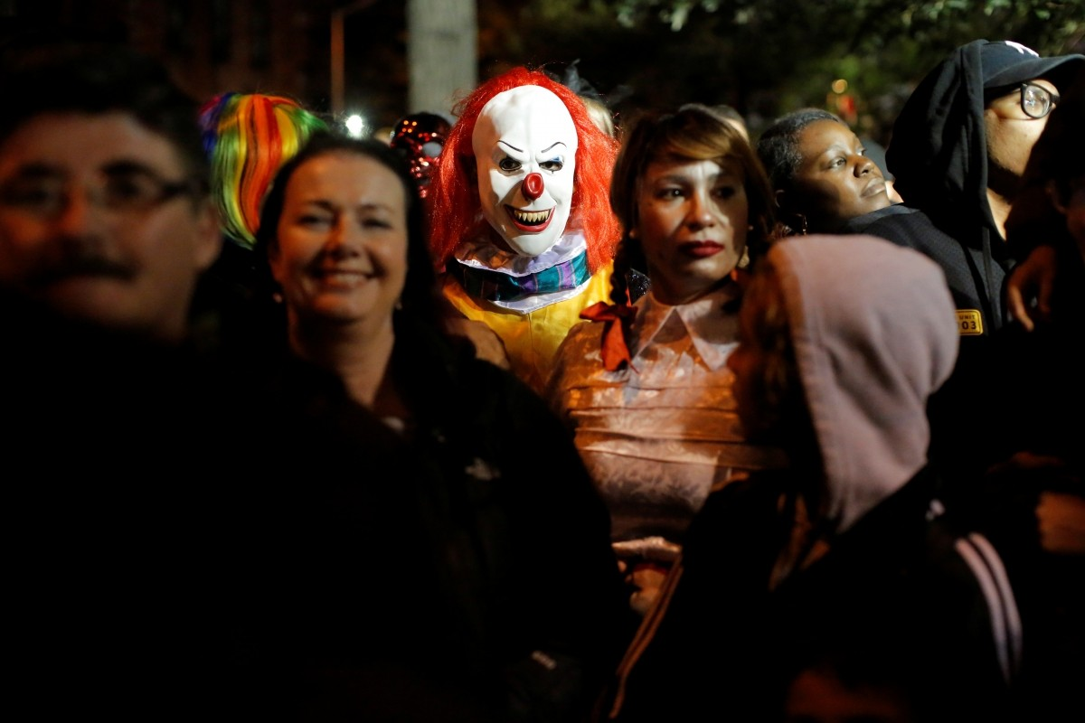 A person dressed in a clown costume stands amongst attendees during the Greenwich Village Halloween Parade in Manhattan, New York, U.S., October 31, 2016.