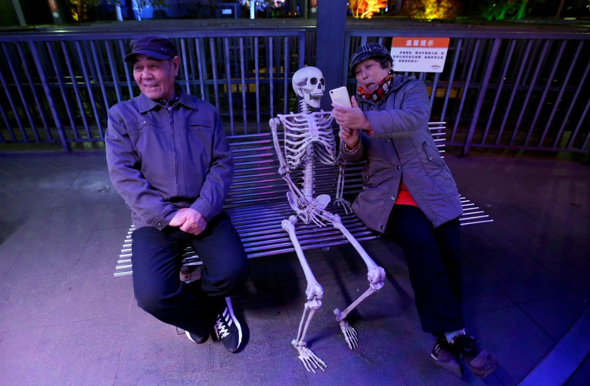 A woman takes a selfie with a fake skeleton next to her husband ahead of a Halloween parade at Happy Valley park in Beijing, China October 31, 2016.