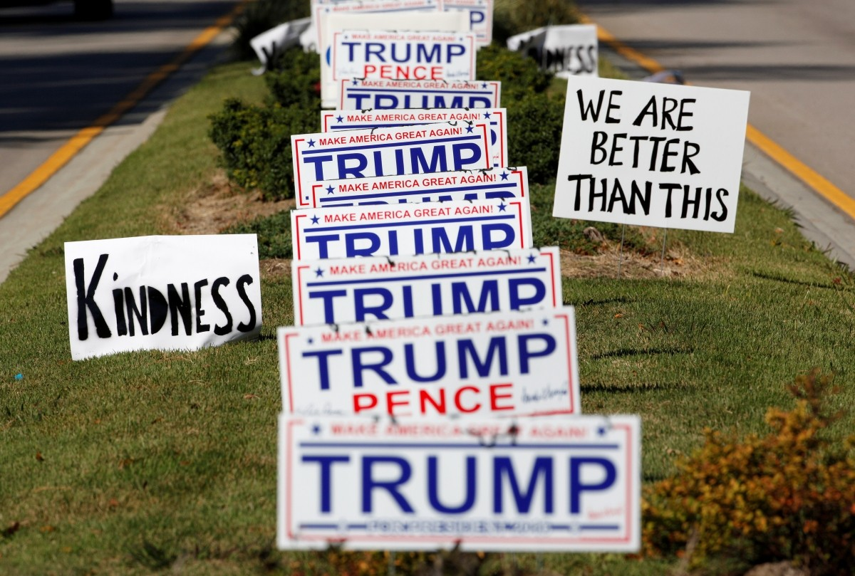 Protest signs urging more civility in American politics flank a long row of signs supporting Donald Trump in Hillsborough, North Carolina